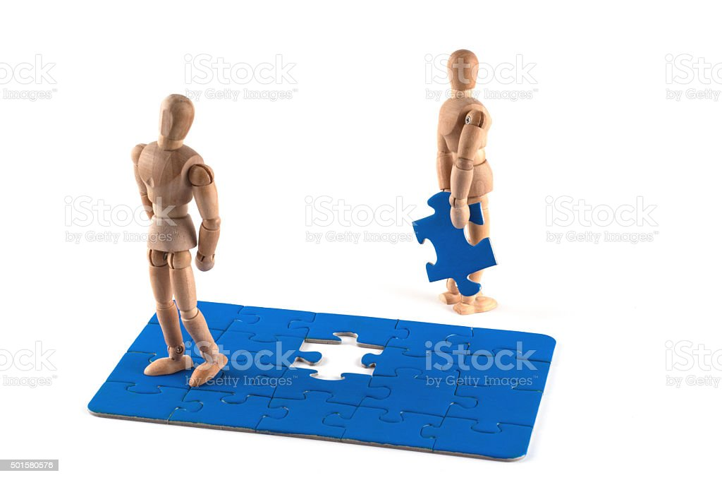 Wooden Mannequin Mediation concepts with jigsaw pieces stock photo