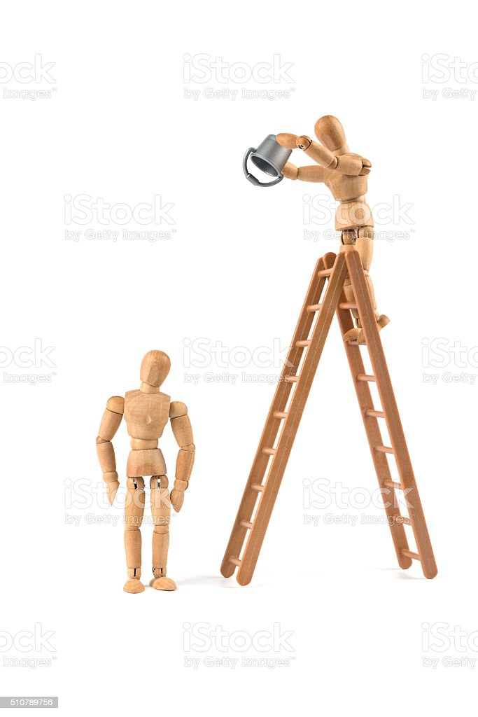 wooden mannequin on ladder pour out bucket on another mannequin stock photo