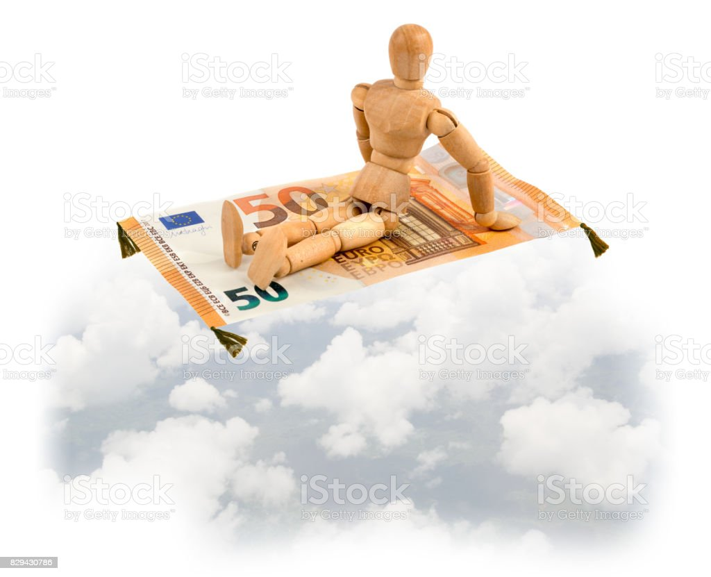 Wooden mannequin on magic carpet of Euro note flying in the sky stock photo