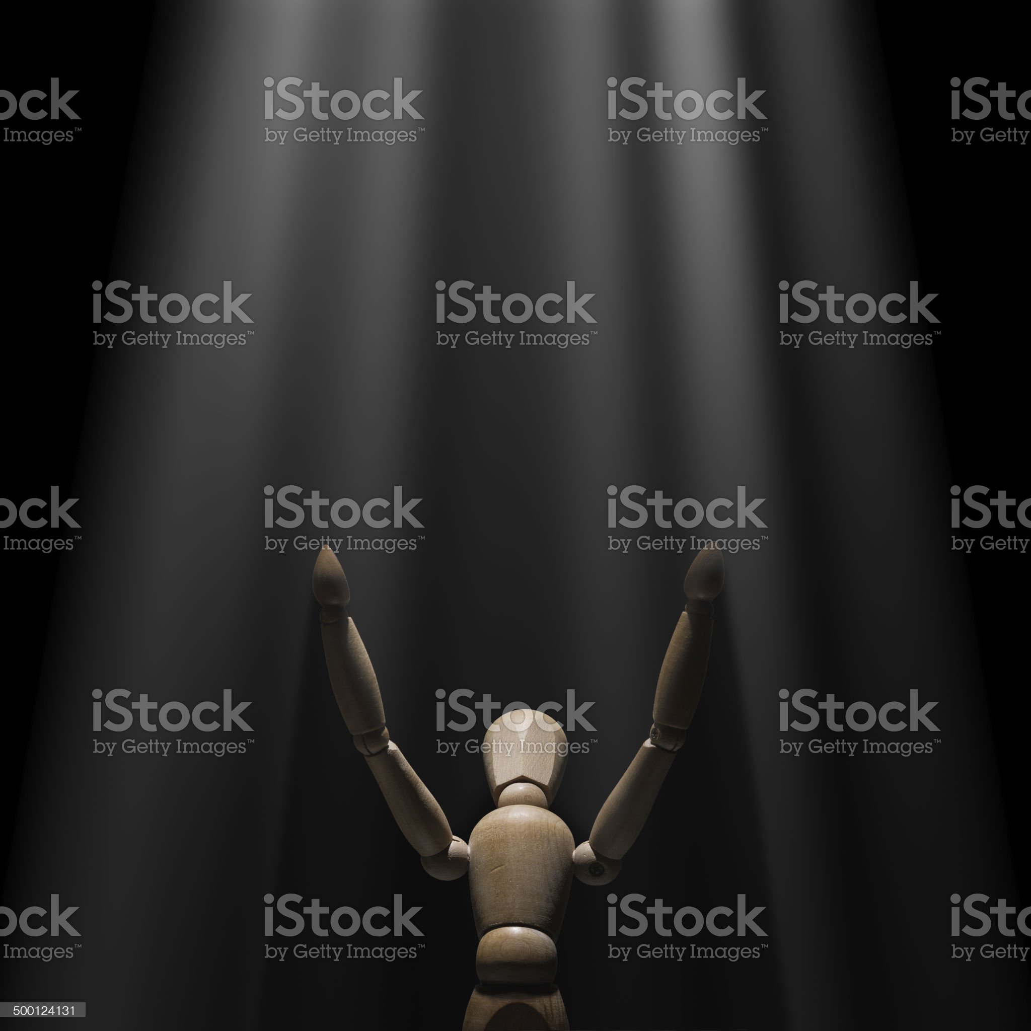 Wooden mannequin raised hands to light royalty-free stock photo