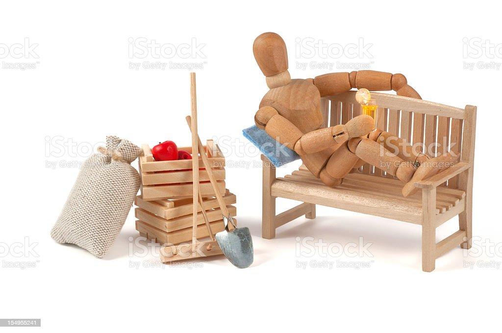 wooden mannequin relaxing after garden work stock photo