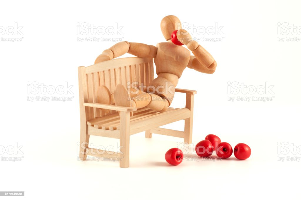wooden mannequin relaxing at a bench and eats apples stock photo