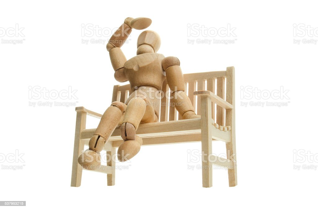 wooden mannequin relaxing at a bench and looking up stock photo