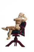 wooden mannequin relaxing on seat and looking in sky