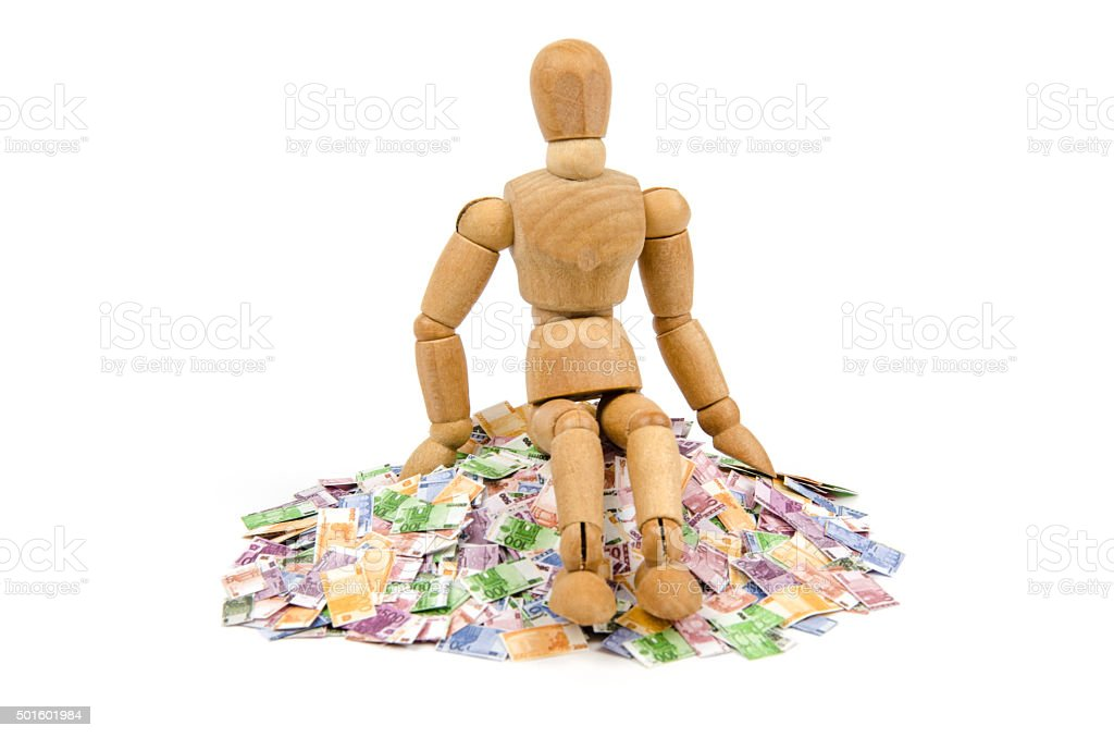 Wooden mannequin sitting on Euro money pile stock photo