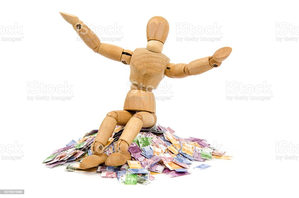 Wooden mannequin sitting on Euro money pile stock photo