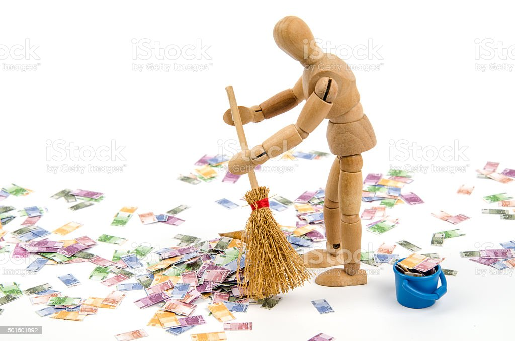 Wooden mannequin sweeping Euro notes with broom stock photo