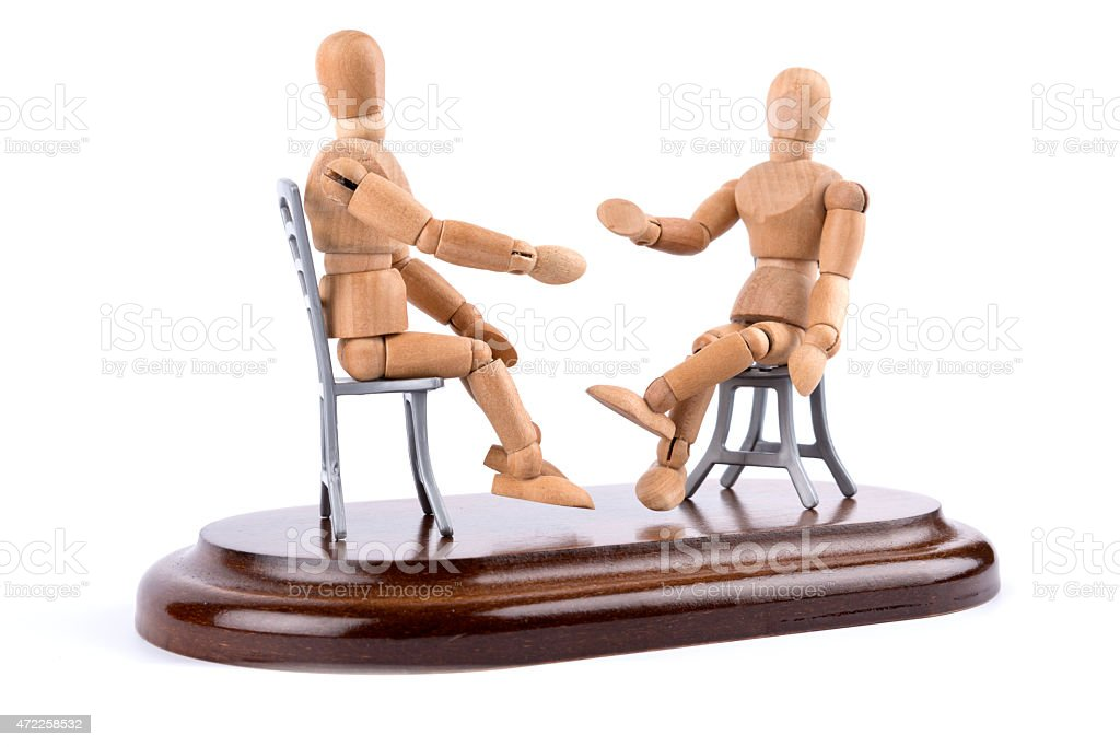 wooden mannequin talking together on chairs - mediation stock photo