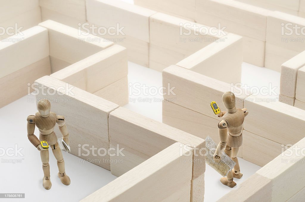 wooden mannequin with GPS in labyinth stock photo