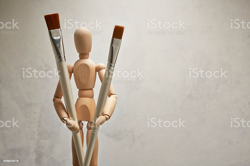 Wooden mannequin with paintbrush stock photo