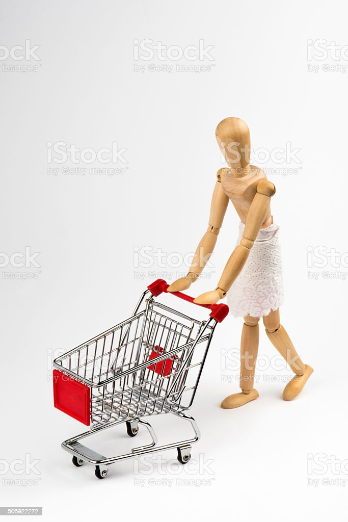 Wooden Mannequin with Shopping Cart stock photo