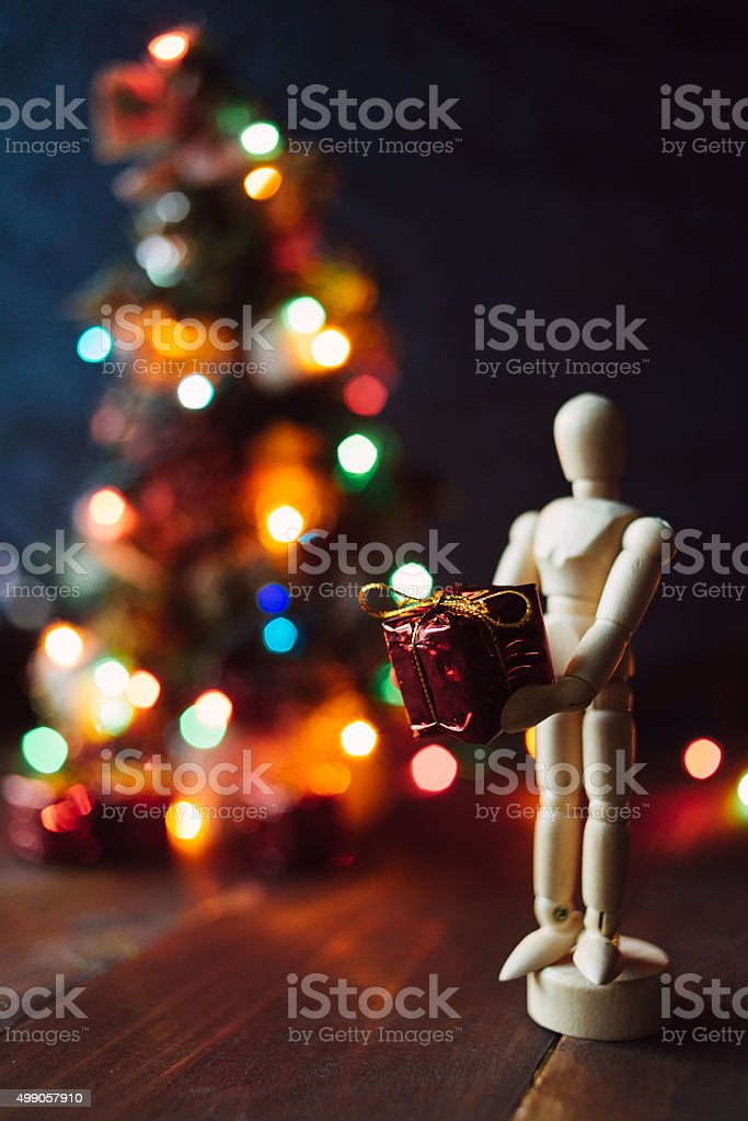 Wooden Mannequin with the gift and the Chritsmas tree stock photo