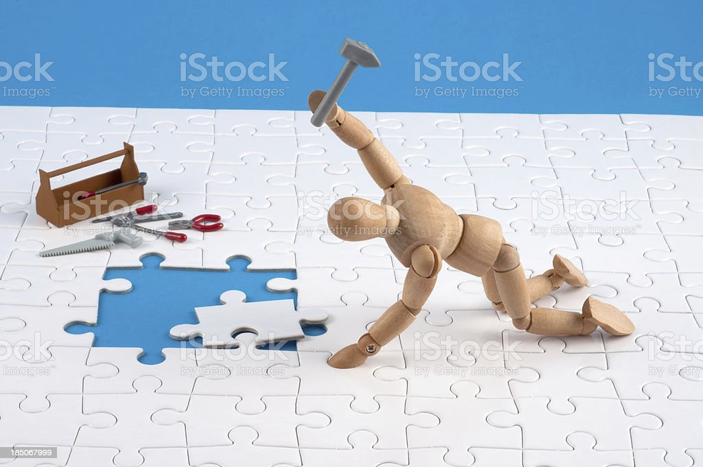 wooden mannequin working hard at a jigsaw. stock photo