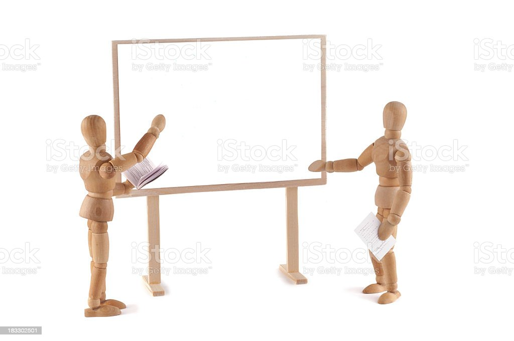 wooden mannequins at whiteboard showing something - copy space stock photo