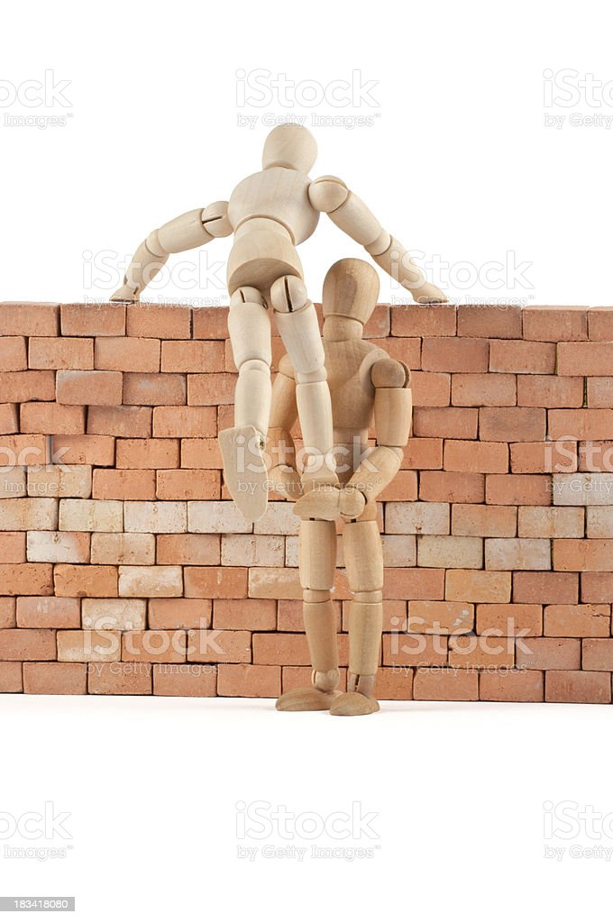 wooden mannequins gives a leg up over the wall stock photo