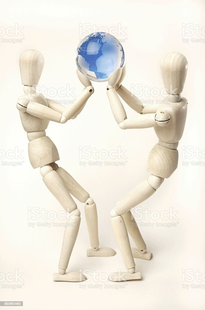 Wooden mannequins holding up glass globe royalty-free stock photo