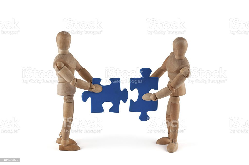 Wooden mannequins putting puzzle together stock photo