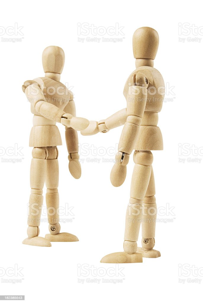 Wooden mannequins shaking hands on white background royalty-free stock photo
