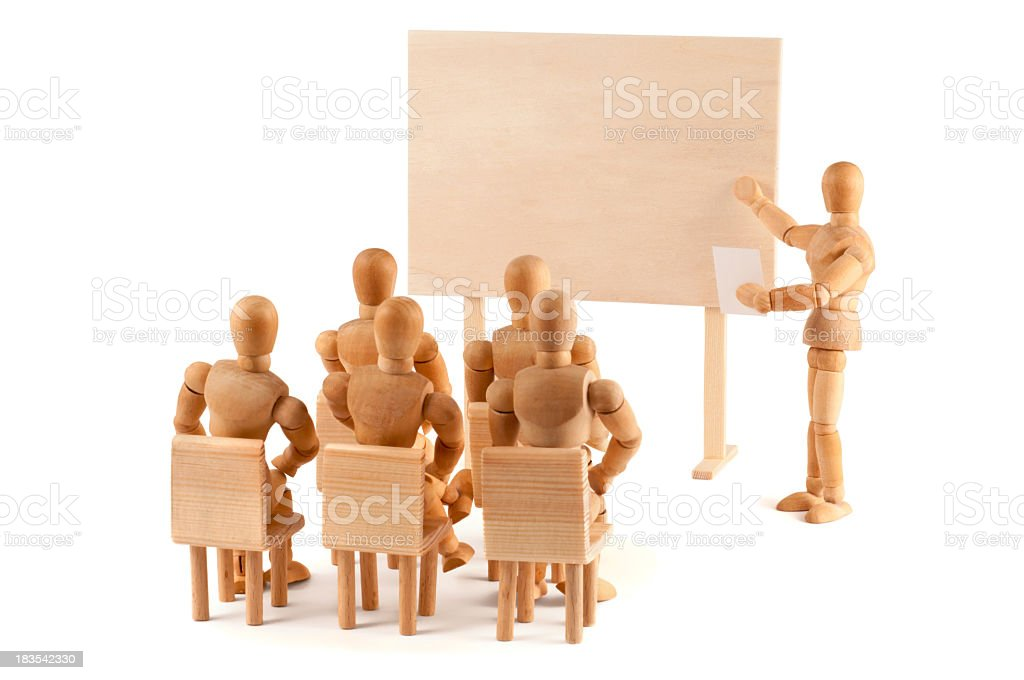 Wooden mannequins sitting in class with mannequin teacher stock photo