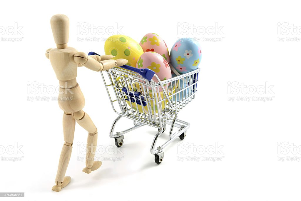wooden manniquine with shopping cart and easter eggs royalty-free stock photo
