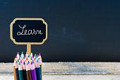 Wooden mini blackboard label with message LEARN