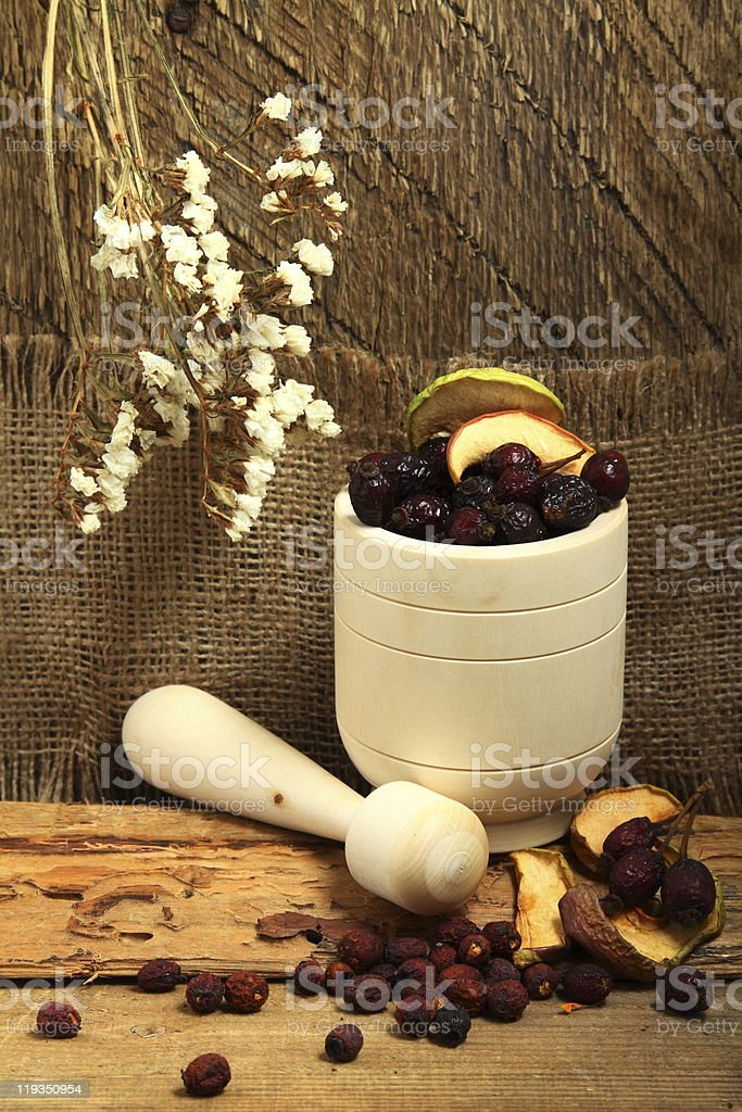Wooden mortar and rose hips royalty-free stock photo