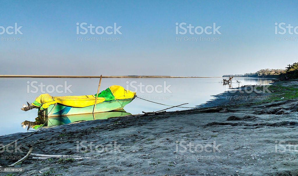 Wooden motor boat on a riverbank stock photo