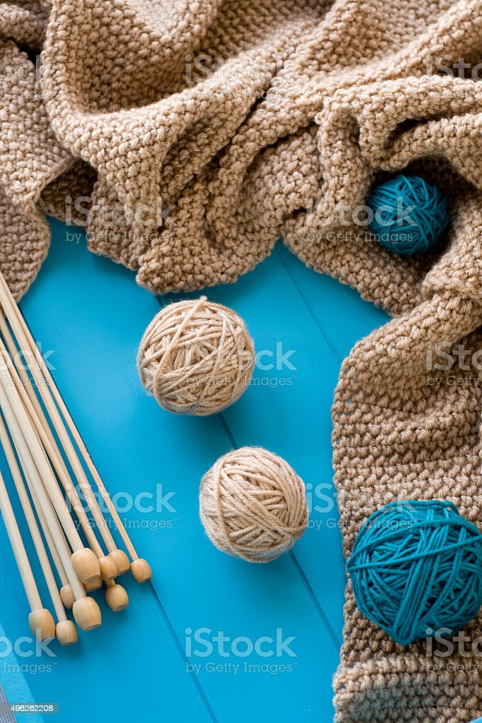Wooden needles lie next to the bright tangle of threads stock photo