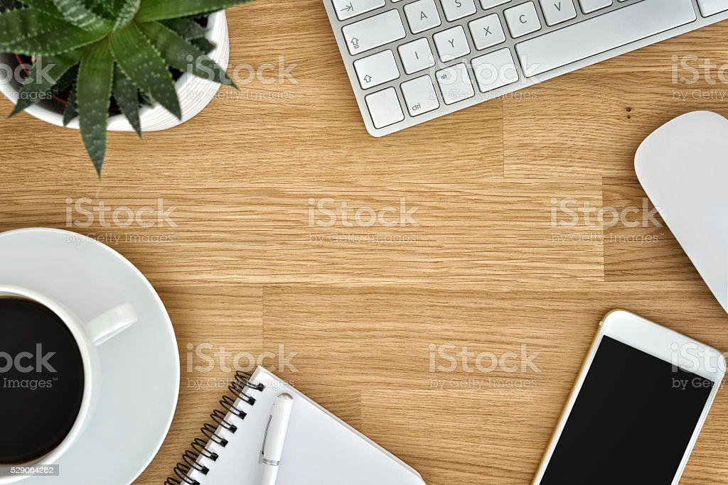 Wooden office table with coffee and computer supplies stock photo