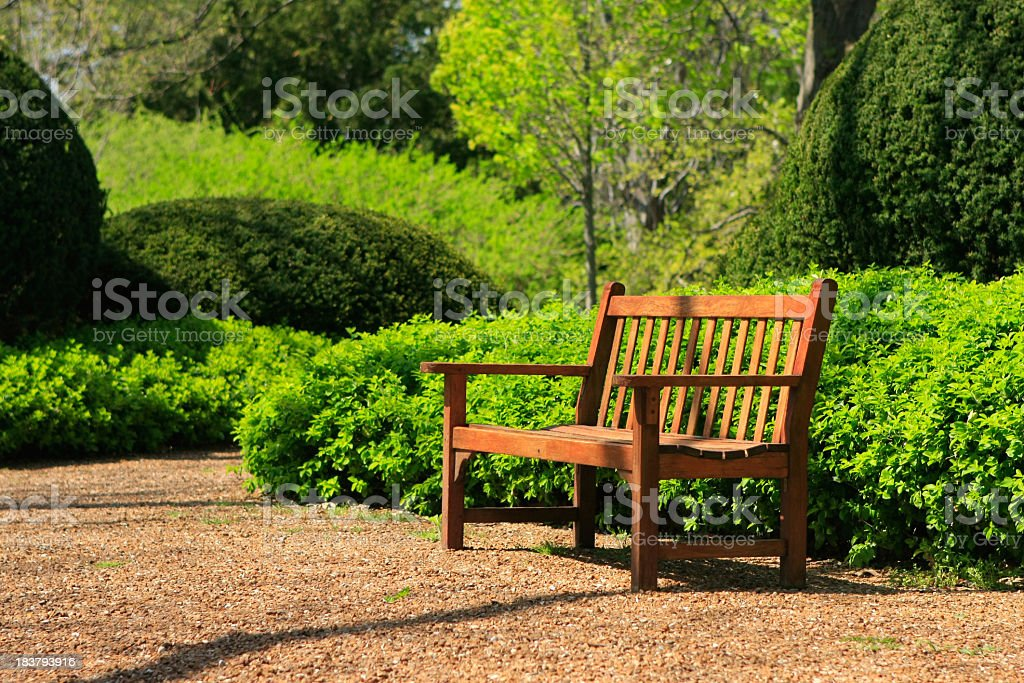 Wooden park bench in a formal garden space stock photo