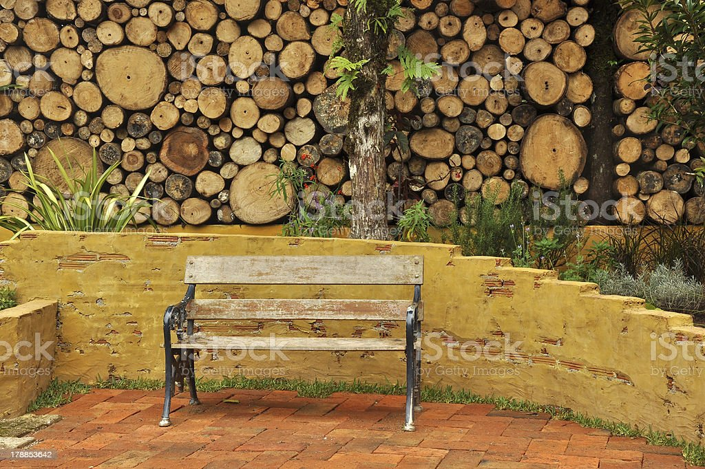 wooden park bench in a log wall royalty-free stock photo