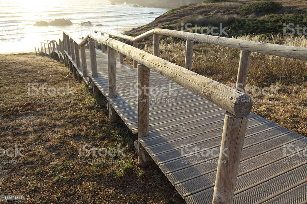 Wooden path to the Amado beach stock photo
