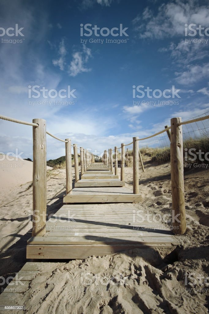 Wooden path to the beach on the dunes. Guincho beach in Cascais, Portugal stock photo