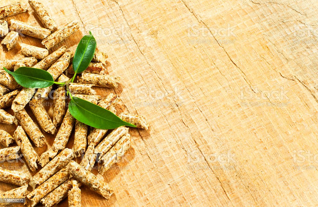 Wooden pellets on a wooden surface with three leaves stock photo