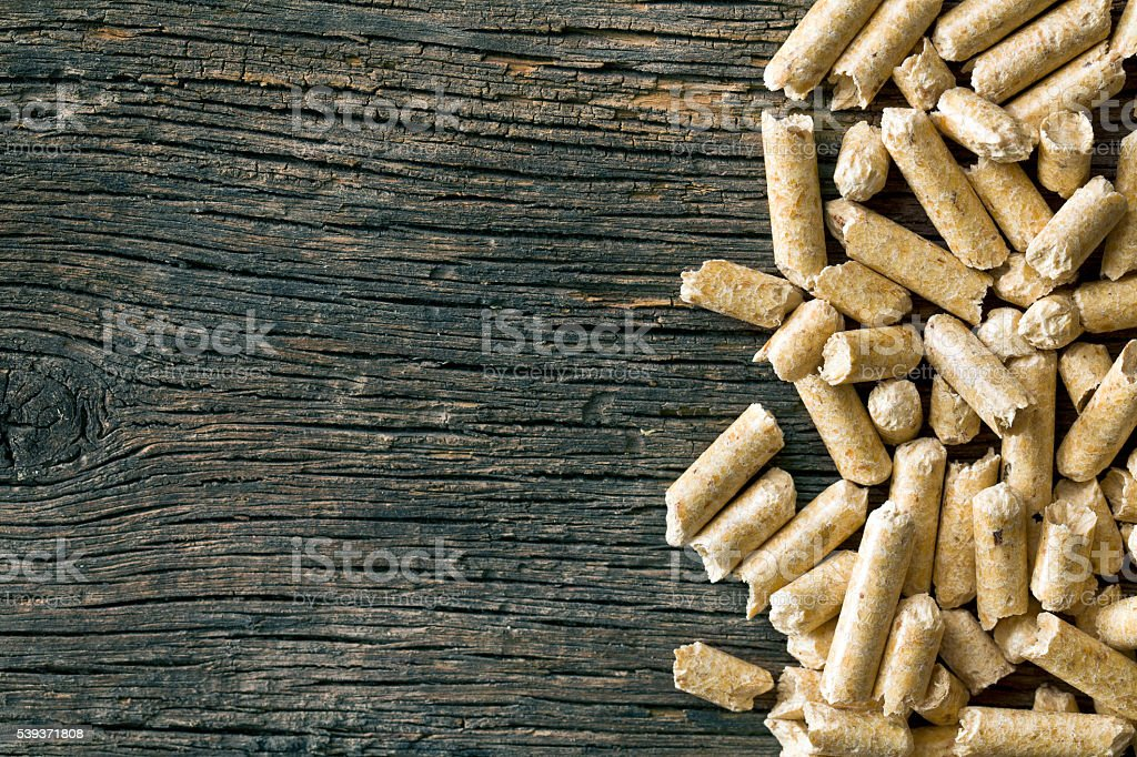 wooden pellets on old wooden background stock photo
