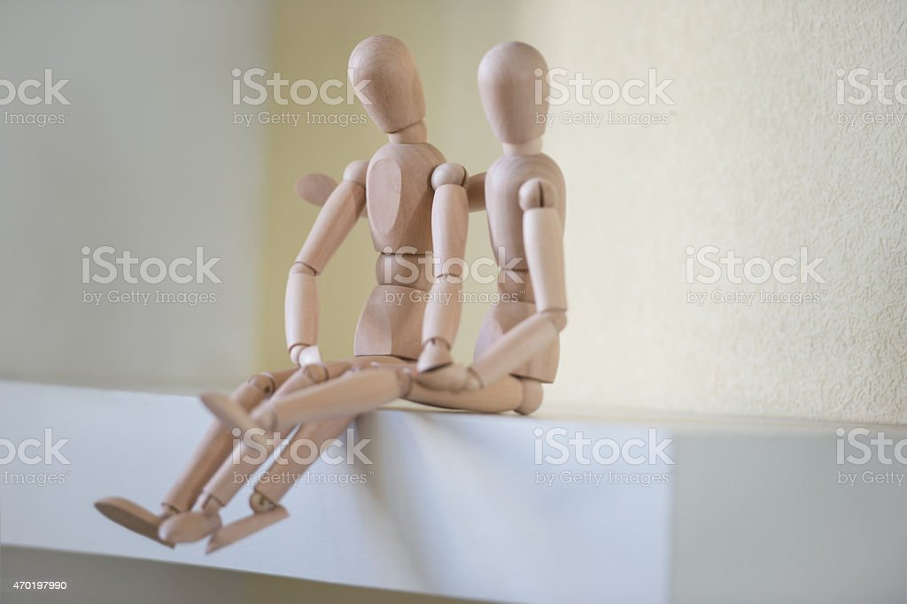 Wooden people sitting at home and hugging. People relationship concept. stock photo