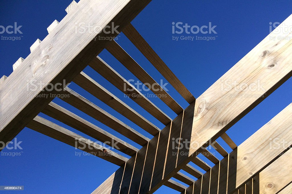 Wooden pergola against blue sky stock photo