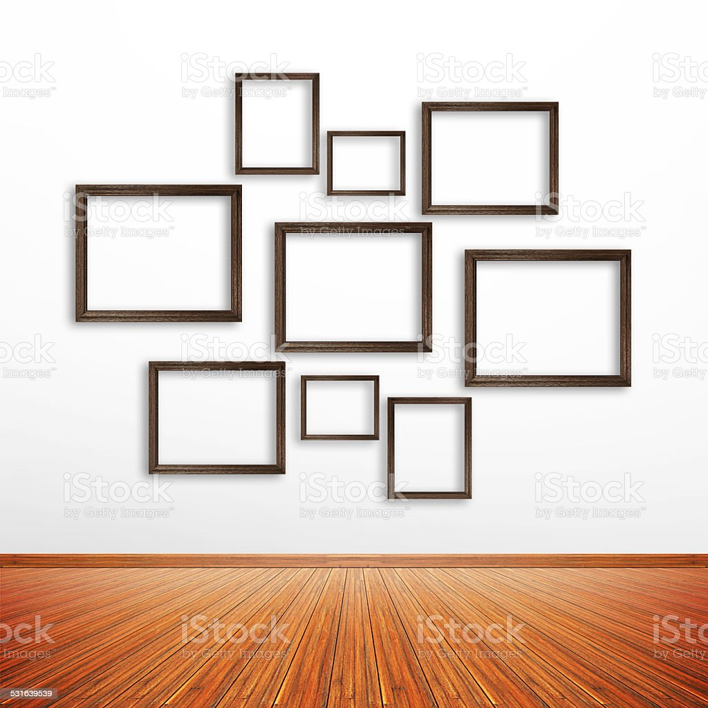 Wooden photo frames on white wall inside the room stock photo