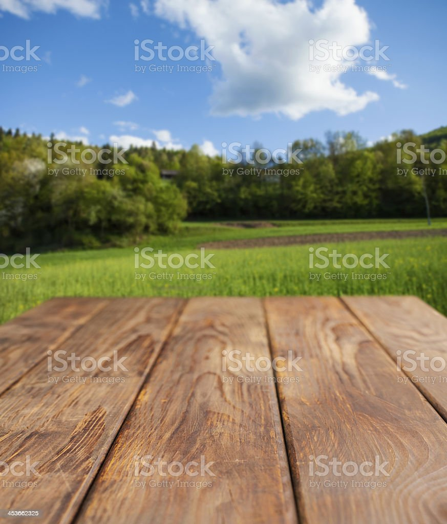 Wooden picnic table against green scenery royalty-free stock photo