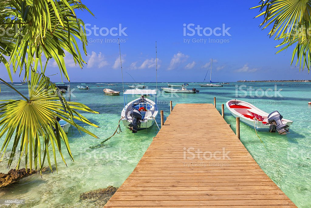 wooden pier and fishing boats on a Caribbean beach stock photo