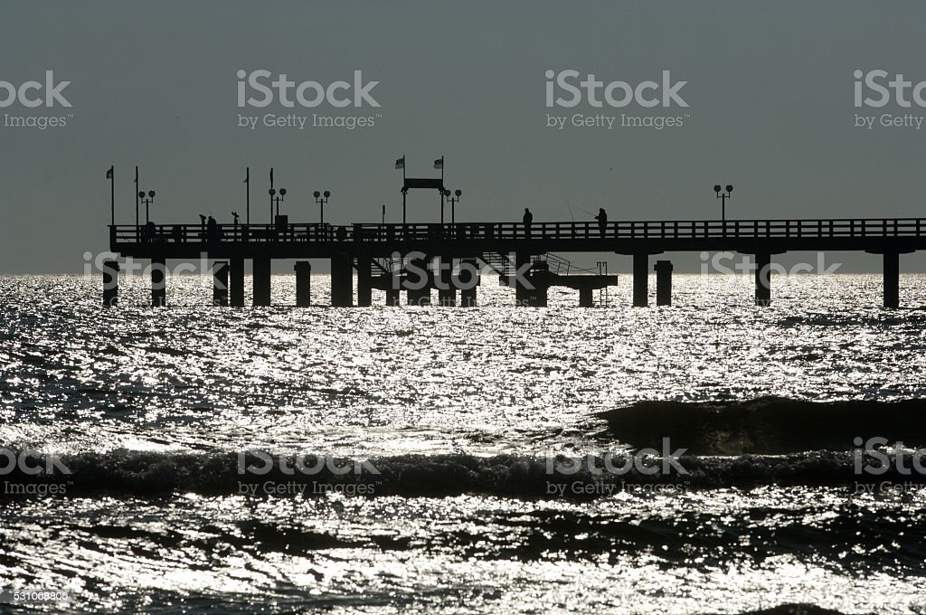 Wooden pier in Baltic see in backlight stock photo