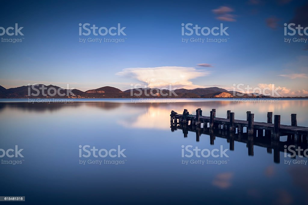 Wooden pier  jetty  blue lake sunset and sky reflection on stock photo