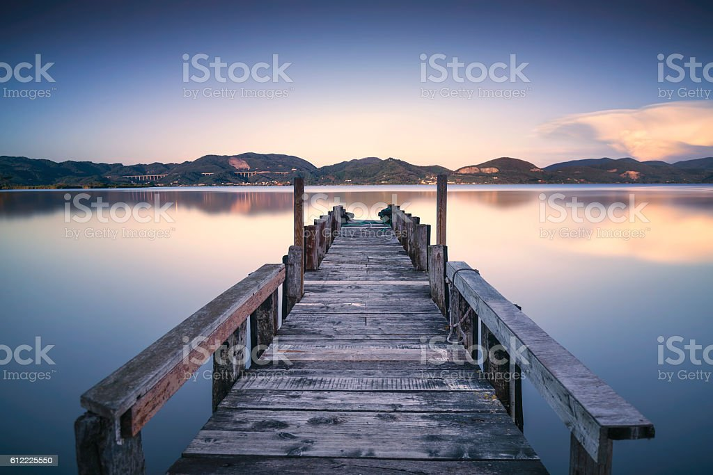 Wooden pier jetty on a blue lake sunset  sky reflection stock photo