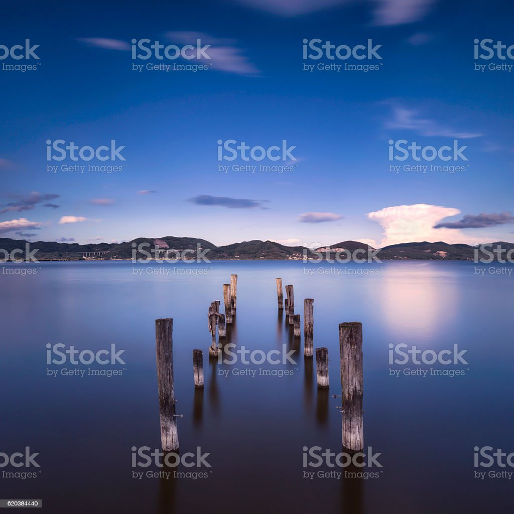 Wooden pier  jetty remains  blue lake sunset and sky refle stock photo