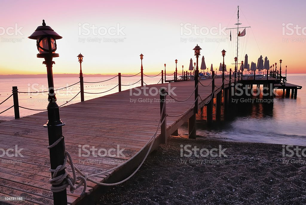 Wooden pier lighted by pink sunrise glow royalty-free stock photo