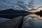 Wooden pier lying on lake, dusk