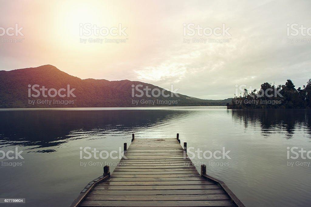 Wooden pier lying on lake Kaniere stock photo