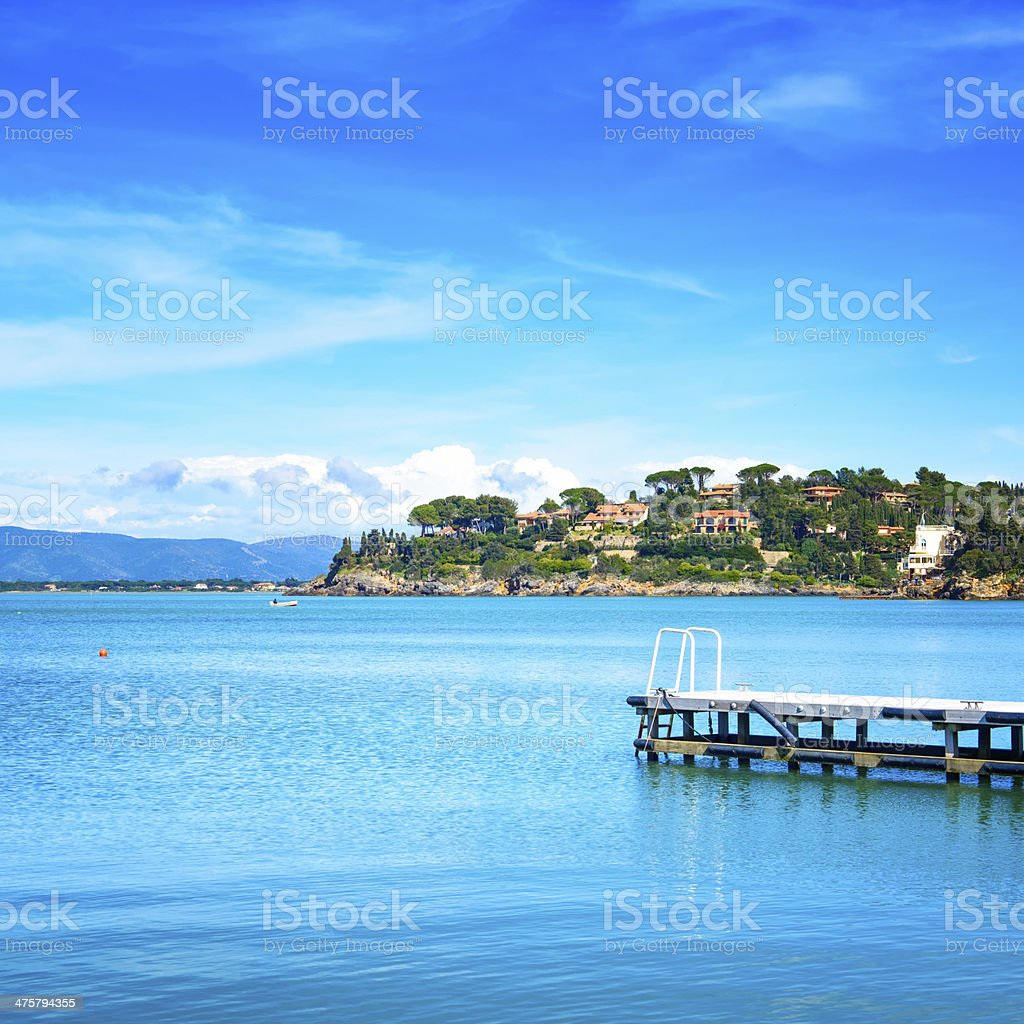 Wooden pier on a blue sea. Beach  Argentario, Tuscany, Italy stock photo