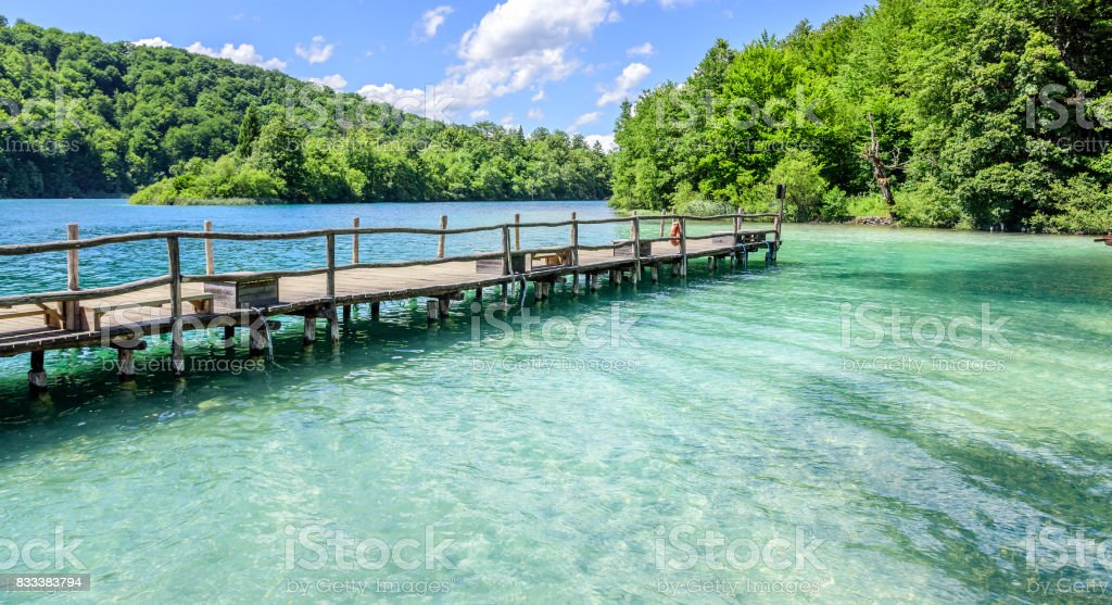 A wooden pier on a mountain lake with clear water stock photo