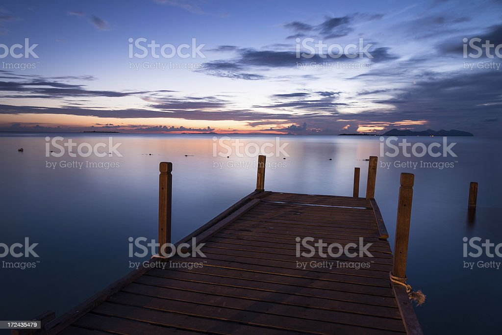 wooden pier on beach with sunset royalty-free stock photo